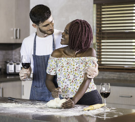 Happy mixed race couple kneading dough together in kitchen