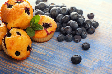 muffin with blueberries on a wooden table. fresh berries and sweet pastries on the board
