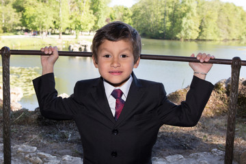 little boy with a jacket and tie in a park