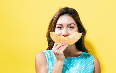 Happy young woman holding a slice of cantaloupe