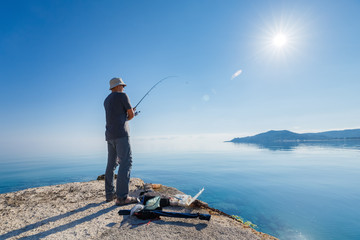 Side view of young man fisherman standing on pier with rod. Seashore of Ionian sea, Zante - Zakinthos island, Greece. Fishing background. Sunrise morning scenery.