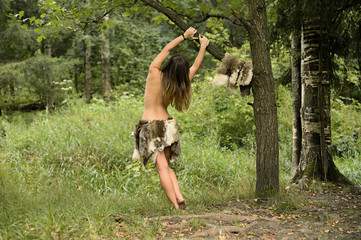 A young maiden hung on a tree branch shirtless