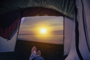 view from a tent on sunset at beach, human legs lying in tourist tent with view of the sea