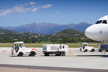 Airport ehicles towing white modern aircraft on the parking lot. Airport ground operation. Ajaccio, Corsica Airport.