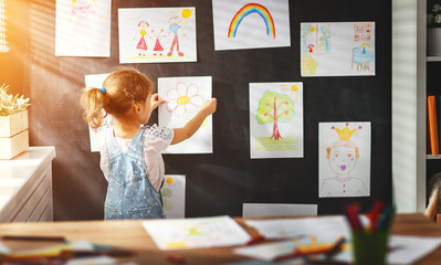 child girl hanging her drawings on wall.