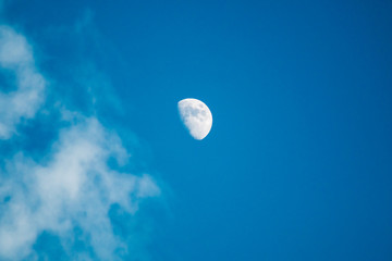 Moon and clouds in the deep blue sky during the day.