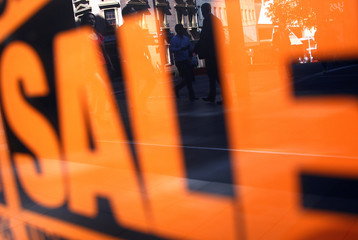 Pedestrians are reflected in the window of a retail shop displaying sales posters in central Sydney, Australia
