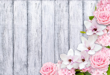 Magnolia flowers with roses and hortense on background of shabby wooden planks in rustic style