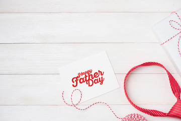 Happy Father's Day with striped tie on wooden background. Greetings and gift box