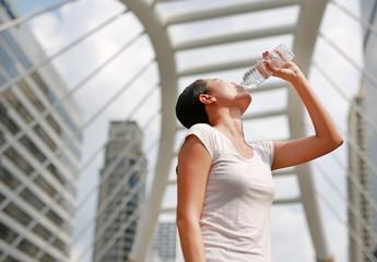 woman drinking water in public area.