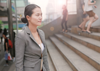 Young business woman walking outside. Asian businesswoman office worker in downtown business district.