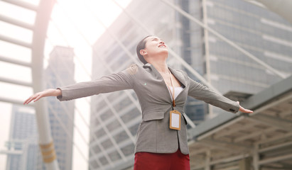 Beautiful young business woman feeling free with arms wide open outside.