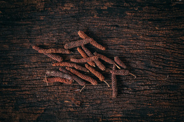 Long Pepper dry on wood background. Indian long pepper, Javanese long pepper (Piper retrofractum Vahl) spices and herbs.