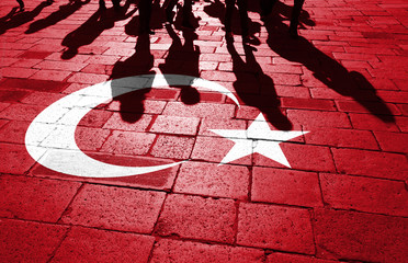 Shadows of group of people walking through the sunny streets with painted Turkey flag on the floor.