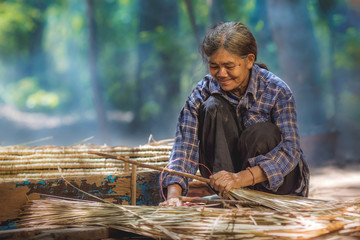 Old asian woman making roof of grass.
