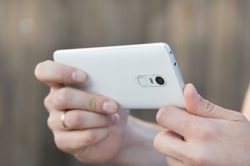 A man takes pictures on a smartphone. Close-up of hand and gadget in a horizontal position