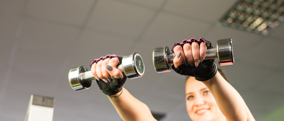 Closeup on fitness woman workout with dumbbell.