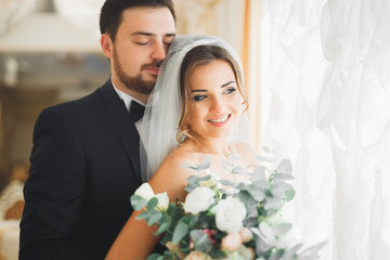 Wedding photo shoot of the newlyweds couple posing in a beautiful hotel