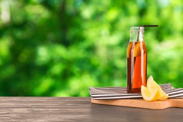 Glass bottle of lemonade tea on blurred background