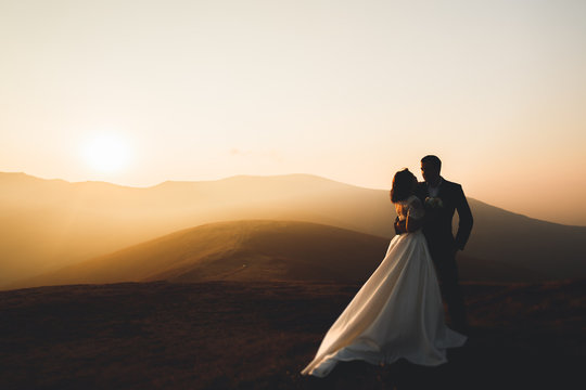Happy beautiful wedding couple bride and groom at wedding day outdoors on the mountains rock. Happy marriage couple outdoors on nature, soft sunny lights
