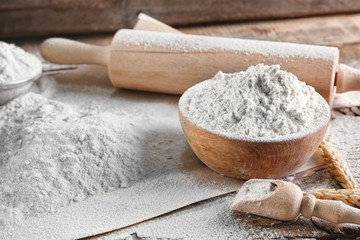 Bowl of flour and rolling pin on wooden background