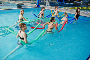 Fitness group of girls doing aerobical excercises in swimming pool at aqua park. Sport and leisure activities.