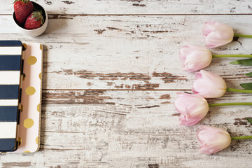 Stunning pink tulips, stripe notebooks and strawberries on white light rustic wooden background. Copy space, floral frame. Wedding, gift card, valentine's day or mothers day background