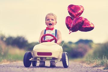 Junge mit Tretauto und Herzballons