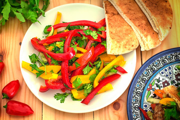 fresh vegetarian salad made with Bulgarian pepper and herbs. Wooden background. Top view. Close-up