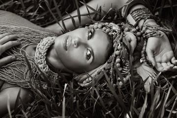 fashion boho beautiful womanl in turban lying on the grass