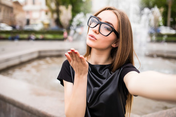 Pretty young woman in glasses making selfie and send kisses