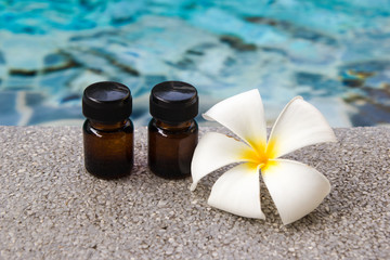 Two bottles of aroma essential oil and flower of frangipani on the swimming pool background for spa theme.