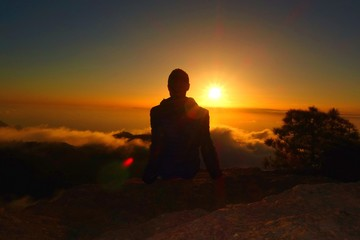 Mountain landscape at sunset with a silhouette of a relaxed teenage boy
