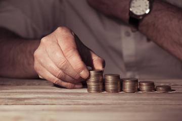 Mann stapelt Geld auf Tisch, Nahaufnahme