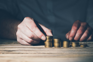 Stacking money coins, business casual man on table