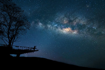 Milky Way at night. Colorful night sky with stars and silhouette of a standing happy man with raised-up arms on the mountain. Freedom travel on long weekend vacation.