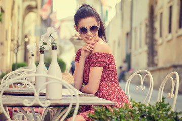 Young woman having italian breakfast with croissant and coffee at the cafe on the street