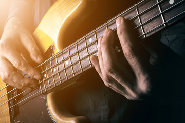 Live rock music background, electric bass guitar over bright blurred stage lights, close up