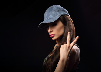 Young sexy female model in blue hat showing victory gesture on dark background with empty copy space.