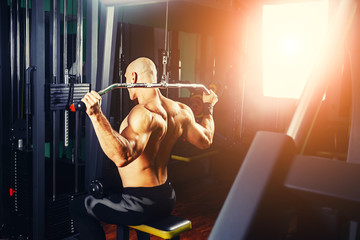 power athletic guy bodybuilder, execute exercise with gym apparatus, on broadest muscle of back