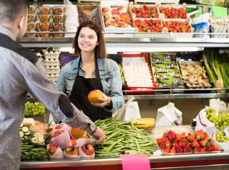 young female seller assisting customer to buy fruit and vegetables in grocery shop