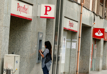 A woman uses a Banco Popular's cash dispenser (ATM) next to a Santander office in Barcelona