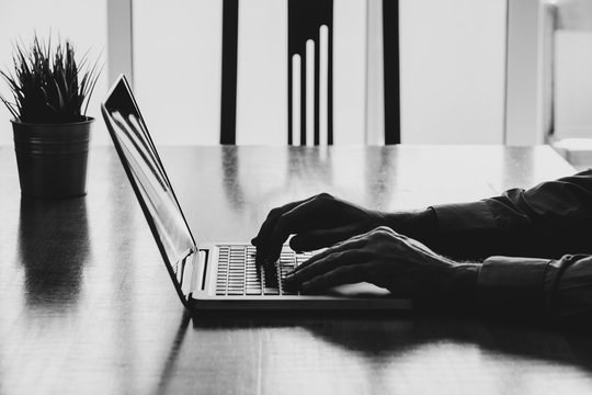 Man hands typing on a laptop in a workplace. Business black and white.