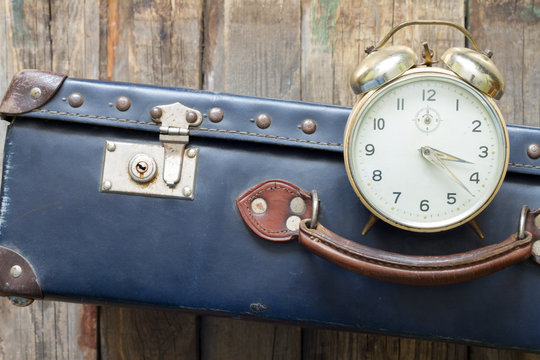 Last minute travel concept with old retro suitcase and alarm clock