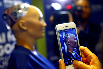 "An attendee takes a picture of Sophia, a robot integrating the latest technologies and artificial intelligence during a presentation at the ""AI for Good"" Global Summit in Geneva"