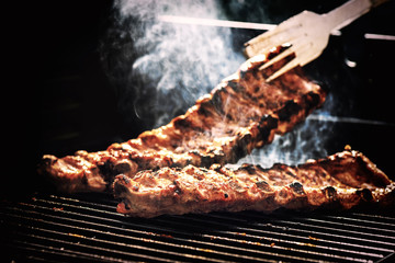 Spare ribs cooking on barbecue grill for summer outdoor party. Food background