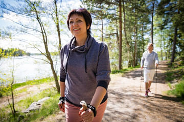 Summer sport in Finland - nordic walking. Man and mature woman hiking in green sunny forest. Active people outdoors. Scenic peaceful Finnish summer landscape. Wall mural