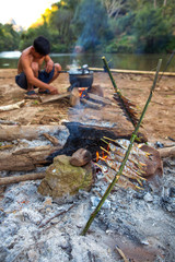 Cooking and Grilling fish on campfire in forest.