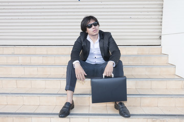 Unemployed asian businessman stress in city outdoor sit on stair