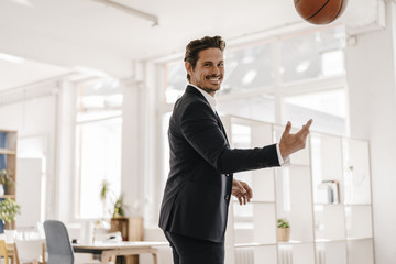 Businessman playing basketball in office